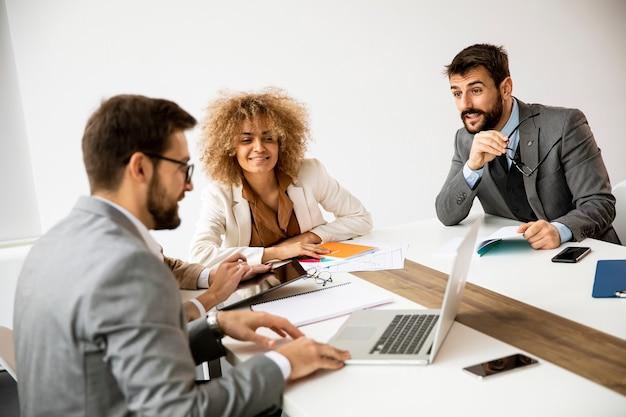 Gruppo multietnico di giovani imprenditori che lavorano insieme e preparano un nuovo progetto in una riunione in ufficio