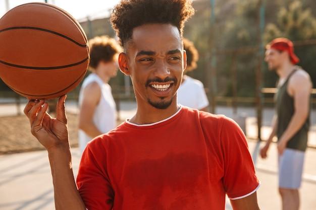 Uomini multietnici che giocano a basket nel parco giochi all'aperto e ragazzo americano che gira la palla al dito