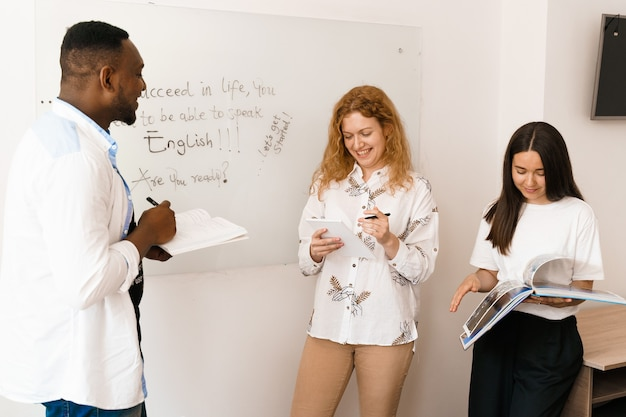 Studenti multietnici e insegnante studiano insieme le lingue straniere in classe