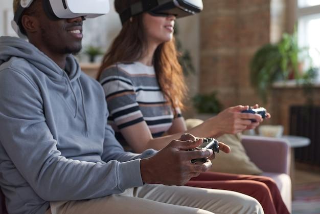 Giovani coppie multietniche con joystick che giocano insieme al videogioco sul divano di casa