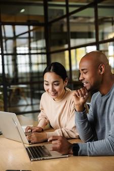 Giovani multietnici e colleghe maschili seduti a tavola e lavorando su laptop in ufficio