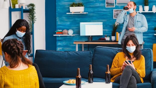 Amici multietnici con maschere protettive che navigano su smartphone seduti sul divano a parlare