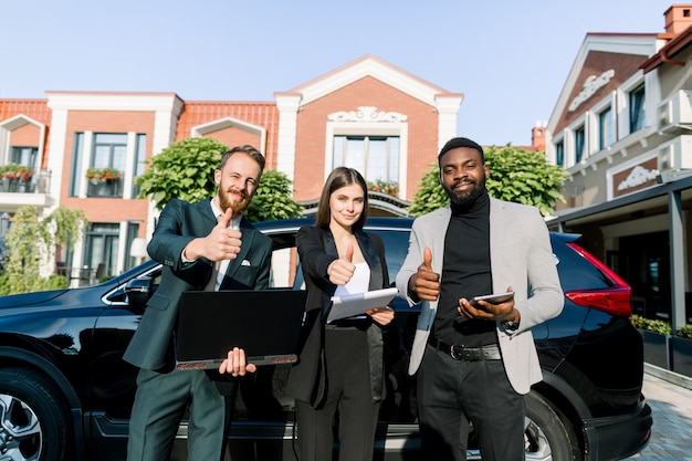 Squadra multietnica di successo, due uomini d'affari e una donna d'affari, con tablet, laptop e documenti, mostrando il pollice in alto, in piedi vicino all'auto all'aperto. concetto di team, business, tecnologia