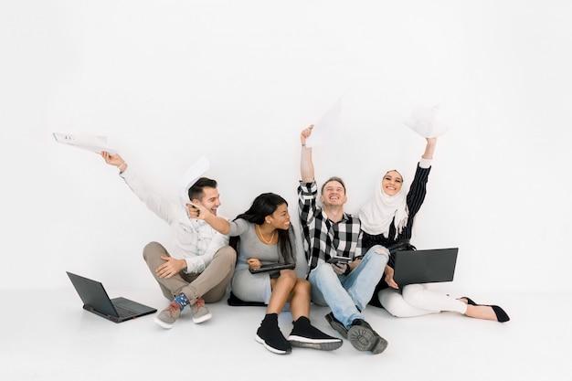 Studenti universitari multietnici, partner commerciali, seduti insieme a terra, usando laptop, lavorando su una nuova startup, felici e soddisfatti