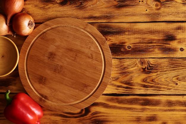 Tagliere circolare in legno multifunzionale per servire pizza, pane o bistecca. vista dall'alto sul tavolo da cucina in legno. rustico. copia spazio