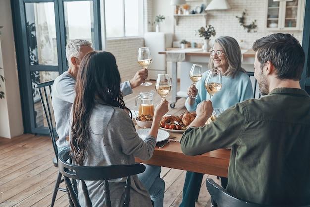 Famiglia multigenerazionale che si brinda a vicenda e sorride mentre cena insieme