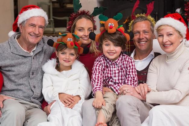 Famiglia multigenerazionale che indossa cappelli di santa sul divano