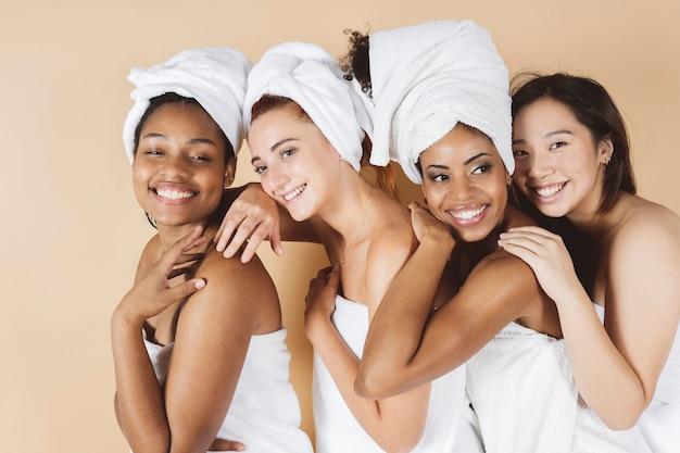 Donne multigenerazionali con pelle e corpo divertenti che si divertono insieme indossando asciugamani per il corpo