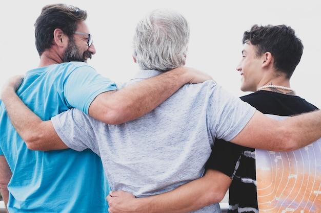 Gruppo familiare multigenerazionale in piedi all'aperto in riva al mare, abbracciati e sorridenti. nonno, figlio e nipote adolescente.