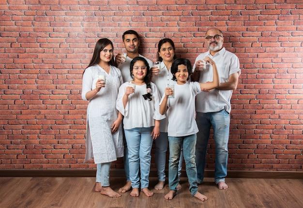 Famiglia asiatica indiana multigenerazionale che mostra o tiene in mano bicchieri pieni di latte contro un muro di mattoni