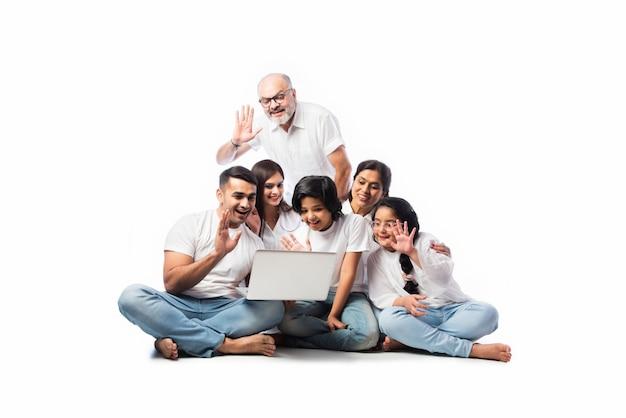 Famiglia asiatica indiana multigenerazionale di sei persone che fanno shopping online utilizzando laptop e scheda elettronica mentre sono seduti su sfondo bianco