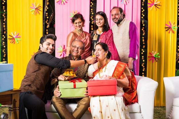 Famiglia indiana multigenerazionale che mangia dolci mentre celebra il festival o l'occasione vestita con abiti tradizionali, seduta sul divano o sul divano