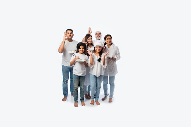 Famiglia indiana multigenerazionale di sei persone che tengono piatto vuoto e ciotole mentre lo chef della bambina indossa il cappello
