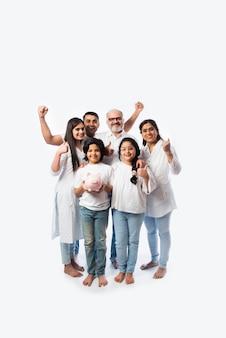 Famiglia indiana multigenerazionale di sei persone che tengono salvadanaio indossando panni bianchi e in piedi contro il muro bianco