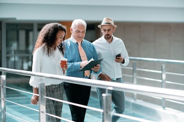 Team aziendale multinazionale con documenti aziendali che attraversano la hall dell'ufficio