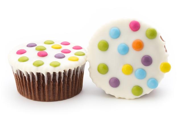 Muffin decorati variopinti multipli su bianco.
