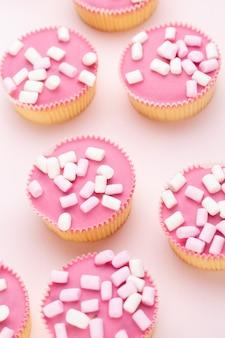 Molteplici muffin colorati ben decorati su uno sfondo rosa, vista dall'alto.