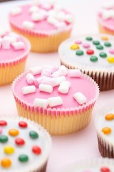 Più muffin colorati ben decorati su uno sfondo rosa, vista dall'alto.