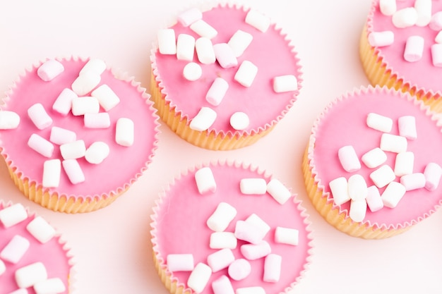 Molteplici muffin colorati ben decorati su una superficie rosa, vista dall'alto.