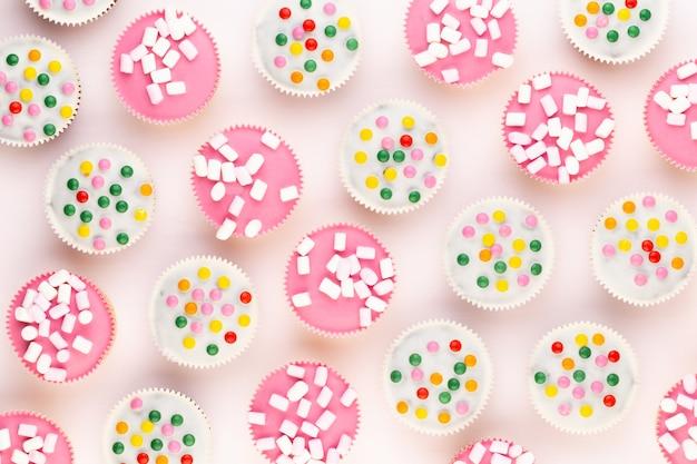 Molteplici muffin colorati ben decorati su uno sfondo bianco, vista dall'alto.