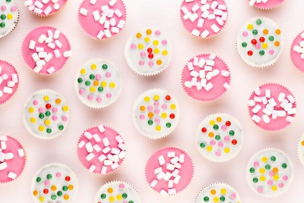 Muffin graziosamente decorati variopinti multipli su un tavolo bianco