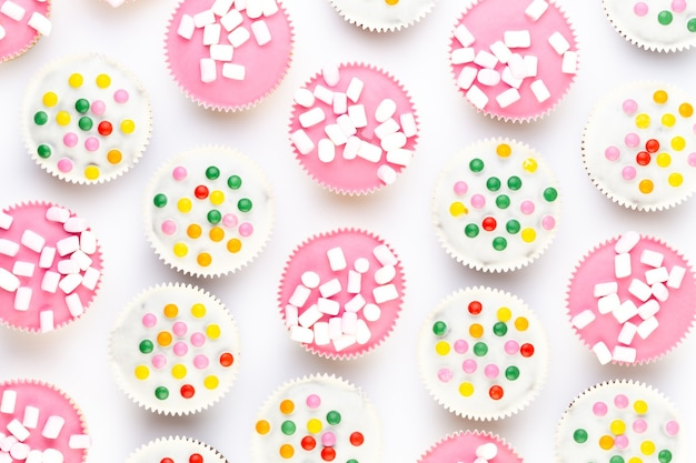 Muffin piacevolmente decorati variopinti multipli su bianco