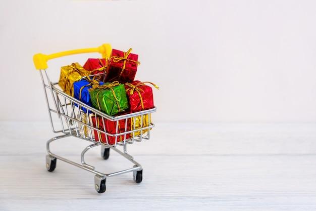 Più colori regalo o regali scatole in un carrello della spesa, per la promozione delle vendite, i premi e il concetto di acquisto online di natale.