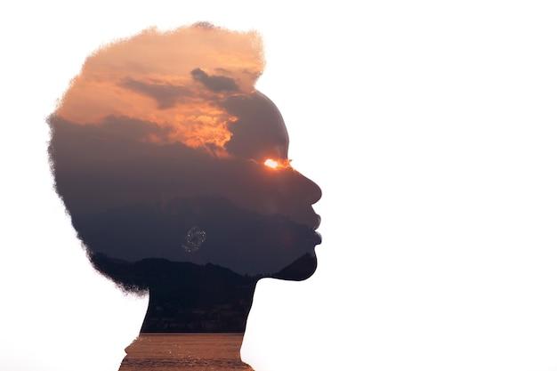 Immagine a esposizione multipla con l'alba e l'occhio in fiamme all'interno della silhouette della donna. psicologia e concetto di controllo della gestione della rabbia.