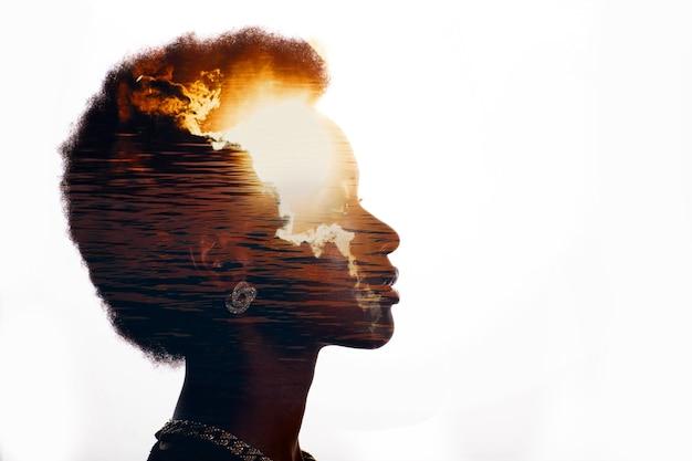 Immagine di esposizione multipla con l'alba e il mare all'interno della silhouette di donna afroamericana. black lives matter stato mentale e concetto di mentalità di libertà.