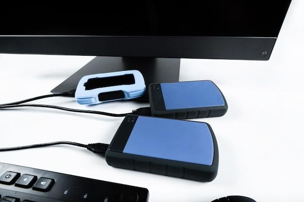 Più dischi rigidi esterni collegati a un monoblocco su sfondo bianco. computer con disco rigido