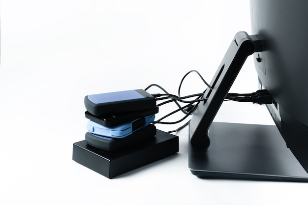 Più dischi rigidi esterni collegati a un monoblocco su uno sfondo bianco. computer con disco rigido.