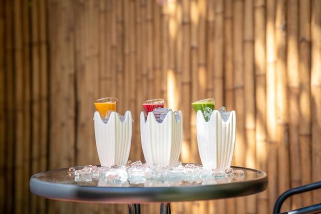 Erbe multiple e miste con succo di frutta a bevanda di colore rosso verde e arancione in vasetto di vetro decorato con ghiaccio intorno.