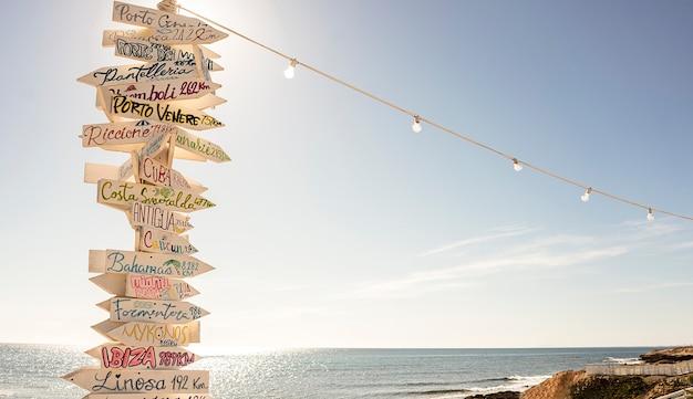 Più segni destinazioni turistiche su un palo di legno in spiaggia in una giornata di sole