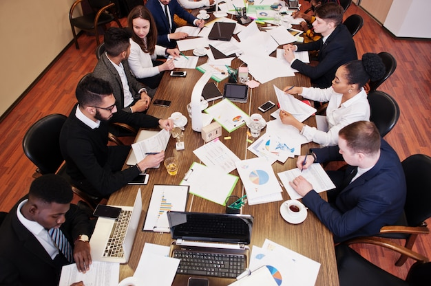 Squadra di affari multirazziale che si rivolge alla riunione intorno al tavolo della sala del consiglio, lavorando insieme e scrivendo qualcosa sui documenti.