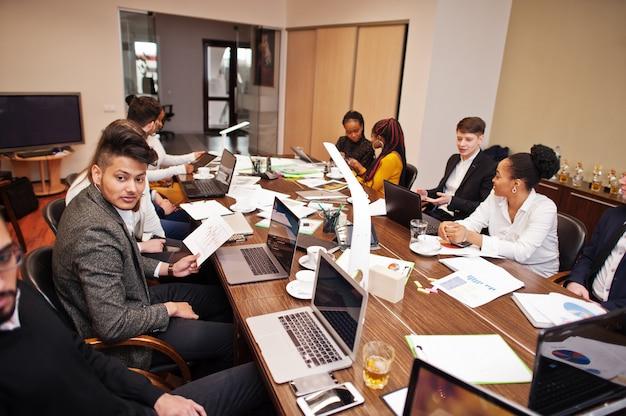 Squadra multirazziale di affari che affronta riunione intorno al tavolo della sala del consiglio.