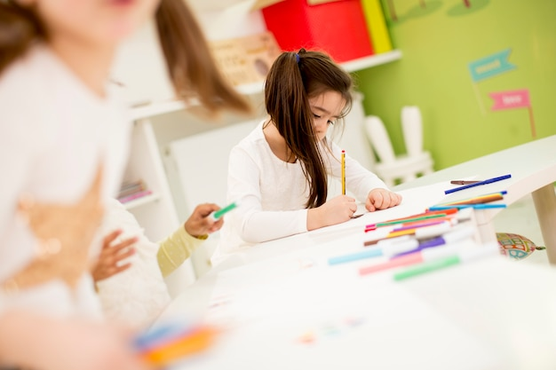 Bambini multirazziali che disegnano nella stanza dei giochi
