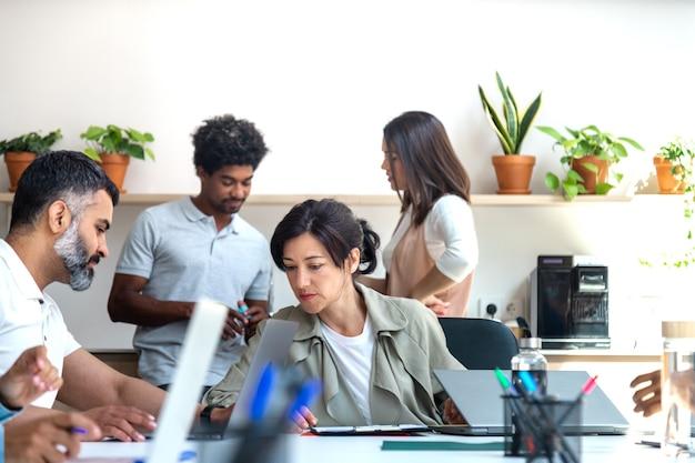 Colleghi multirazziali che lavorano in ufficio colleghi in piedi sullo sfondo affari