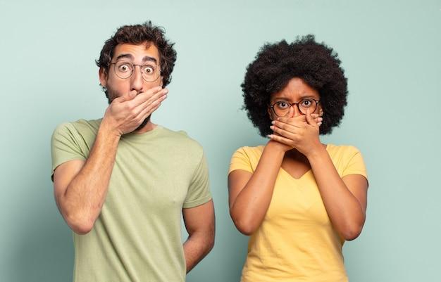Coppia multirazziale di amici che coprono la bocca con le mani con un'espressione scioccata e sorpresa, mantenendo un segreto o dicendo oops