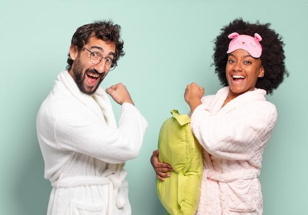 Coppia multirazziale di amici che si sente felice, positiva e di successo, motivata quando affronta una sfida o celebra buoni risultati. pigiama e concetto di casa