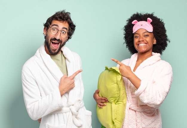 Coppia multirazziale di amici che sembrano eccitati e sorpresi che indicano il lato e verso l'alto per copiare lo spazio. pigiama e concetto di casa