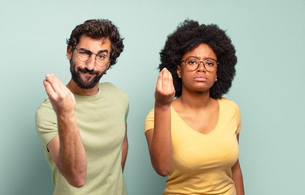 Coppia multirazziale di amici che fanno un gesto di capice o denaro, dicendoti di pagare i tuoi debiti!