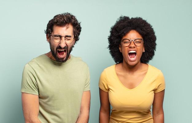Coppia multirazziale di amici che gridano in modo aggressivo, sembrano molto arrabbiati, frustrati, oltraggiati o infastiditi, gridano di no