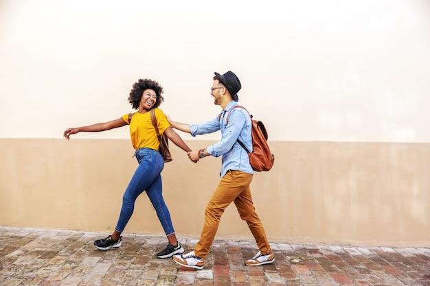 Coppia multirazziale in piedi all'aperto in una bella giornata di sole flirtare per strada mentre si cammina.