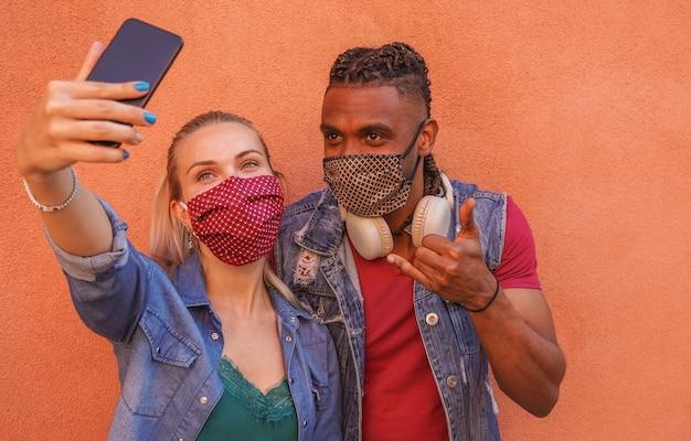 Coppia multirazziale che si fa selfie con maschera facciale su - concetto covid-19