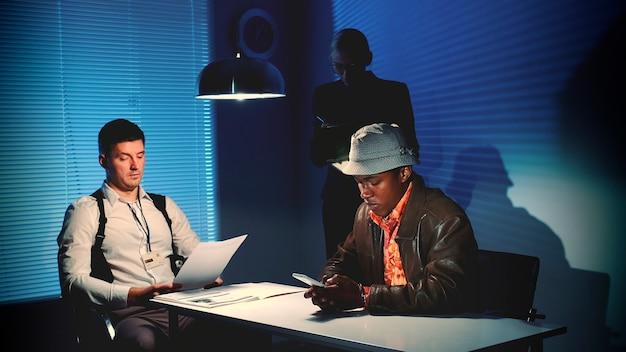 Criminale disperato multirazziale che scrive l'ultimo messaggio sullo smartphone nella stanza degli interrogatori