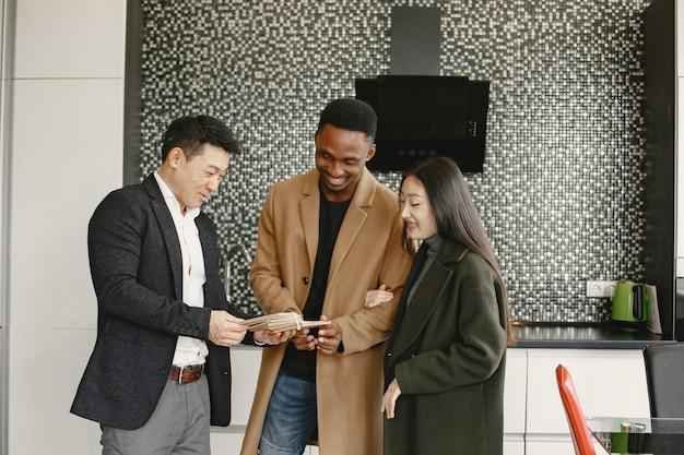 Famiglia multirazziale che ottiene consultazione a casa. scelta dei colori per il pavimento.
