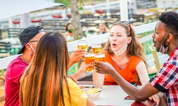 Amici multirazziali che esultano con la birra e sorridono ridendo l'uno con l'altro concetto di maschera facciale di coronavirus
