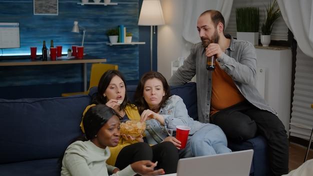 Amici multirazziali che si rilassano sul divano in soggiorno durante la serata al cinema