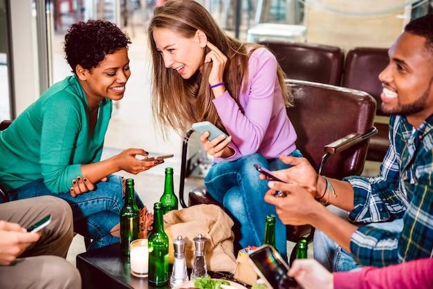 Amici multirazziali che bevono birra e si divertono con i telefoni cellulari intelligenti al ristorante cocktail bar
