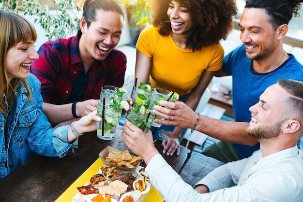Amici multirazziali che si godono l'happy hour che tostano cocktail mojito freschi all'open bar